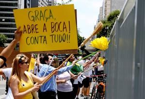 Manifestantes fazem faxinaço na frente da sede da Petrobras, na avenida Paulista, em São Paulo, em protesto contra a corrupção na empresa Foto: Fernando Donasci / Agência O Globo