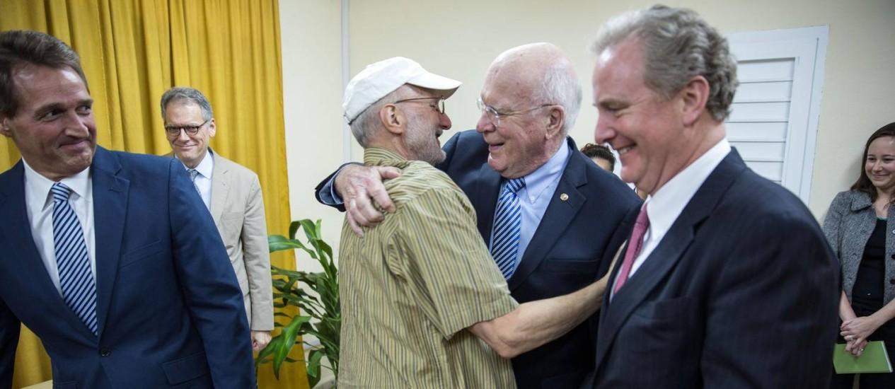 Alan Gross (centro) abraça o senador democrata Patrick Leahy, ao lado do republicano Jeff Flake (esquerda), e do congressita democrata Chris Van Hollen (direita). Aproximação com Cuba dividiu opiniões nos dois partidos Foto: HANDOUT / REUTERS
