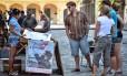 Memorabília. Turistas observam cartazes em Havana: plano de Obama prevê que cartões de crédito e débito de empresas americanas poderão ser usados em Cuba