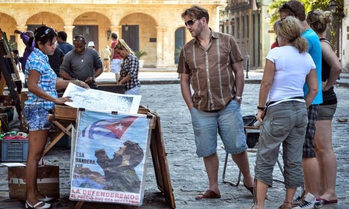 Turistas olham cartazes à venda em Havana Foto: ADALBERTO ROQUE / AFP