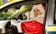 De táxi. Vestido de Papai Noel, Almeida Albernaz, é um dos motoristas que participam da promoção