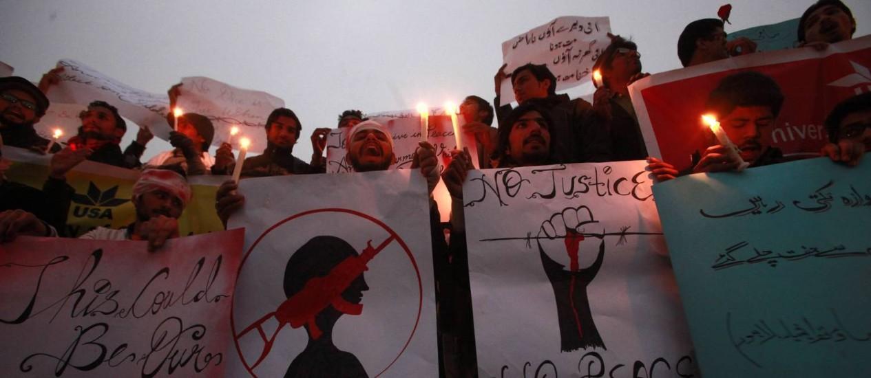 Paquistaneses usam velas e cartazes para condenar o ataque talibã que matou quase 150 pessoas em uma escola de Peshawar Foto: MOHSIN RAZA / REUTERS