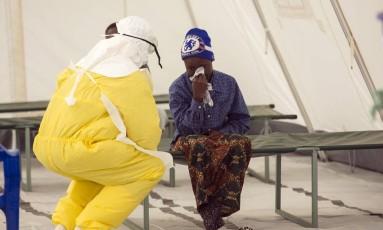 Agente de saúde consola mulher suspeita de ter contraído o vírus em uma zona de quarentena da Cruz Vermelha na vila de Koidu, capital do distrino de Kono Foto: BAZ RATNER / REUTERS