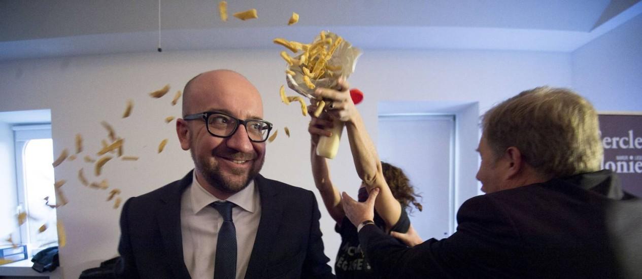 Primeiro-ministro belga, Charles Michel, é atacado com batatas fritas por feministas do grupo LilithS em Namur Foto: LAURIE DIEFFEMBACQ / AFP