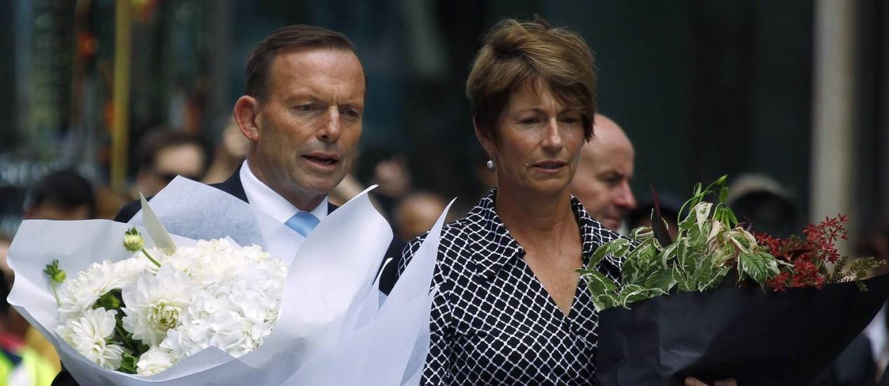 Primeiro-ministro australiano, Tony Abbott, leva flores ao Lindt Café, em Sydney, palco de ataque realizado pelo clérigo iraniano Man Haron Monis Foto: DAVID GRAY / REUTERS