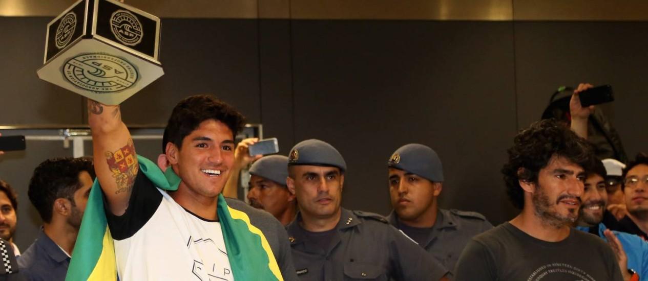Surfista precisou ser escoltado para deixar o aeroporto internacional de São Paulo. Foto: Fernando Donasci / Agência O Globo