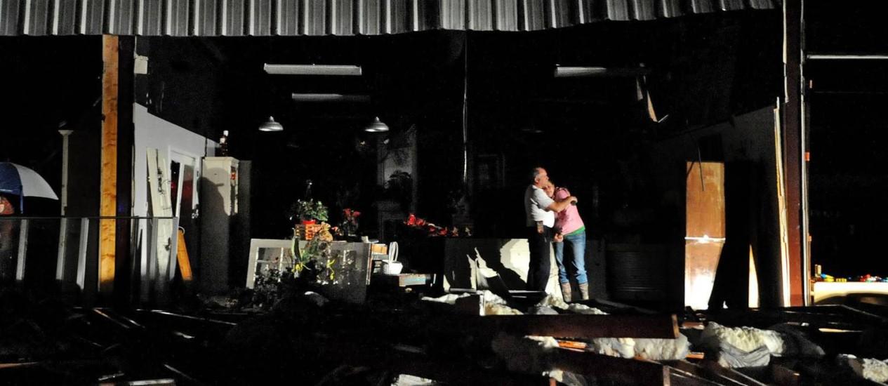Jeff e Melissa McKenzie se abraçam em frente aos destroços da floricultura deles, em Columbia Foto: Eli Baylis / AP