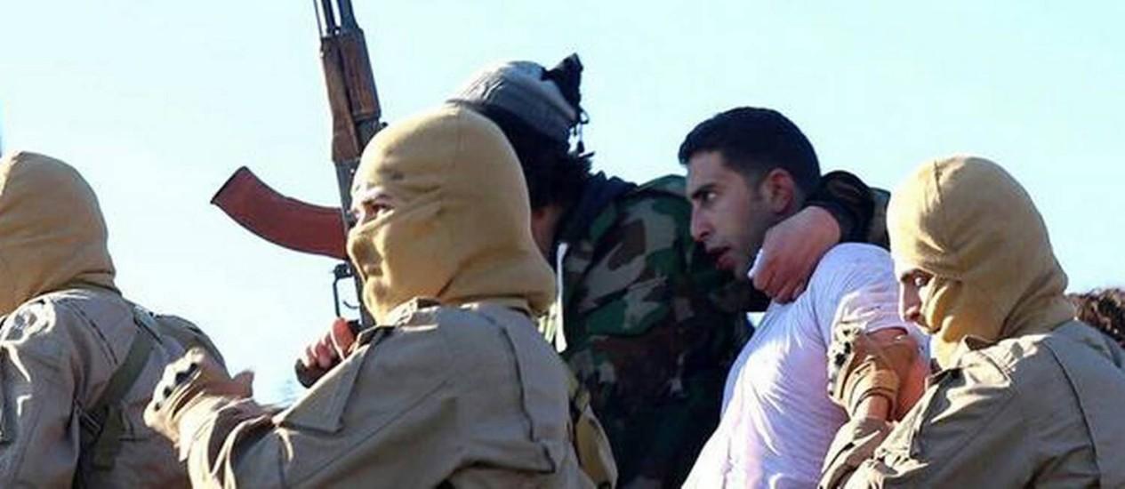 Imagem divulgada pelo Estado Islâmico mostra piloto jordaniano Moaz al-Kassasbeh sendo conduzido por jihadistas. EUA afirma que apoiarão esforços para libertar piloto capturado em Raqqa Foto: Uncredited / AP