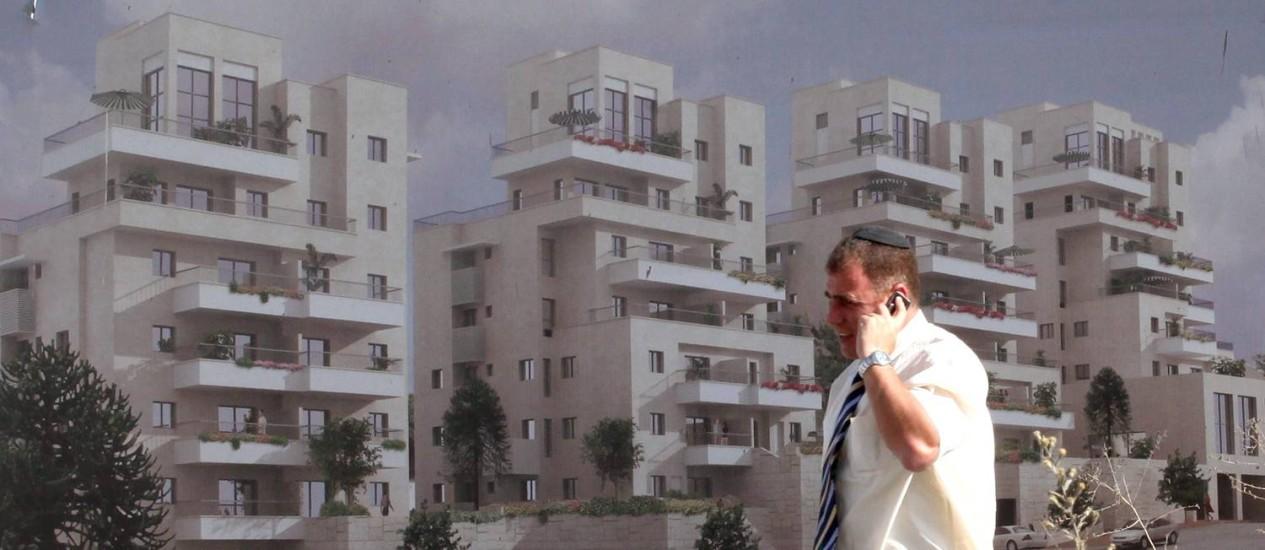 Homem caminha por outdoor que anuncia novas construções em Har Homa, na Cisjordânia. Expansão dos assentamentos judaicos é criticada por potências internacionais Foto: GALI TIBBON / AFP