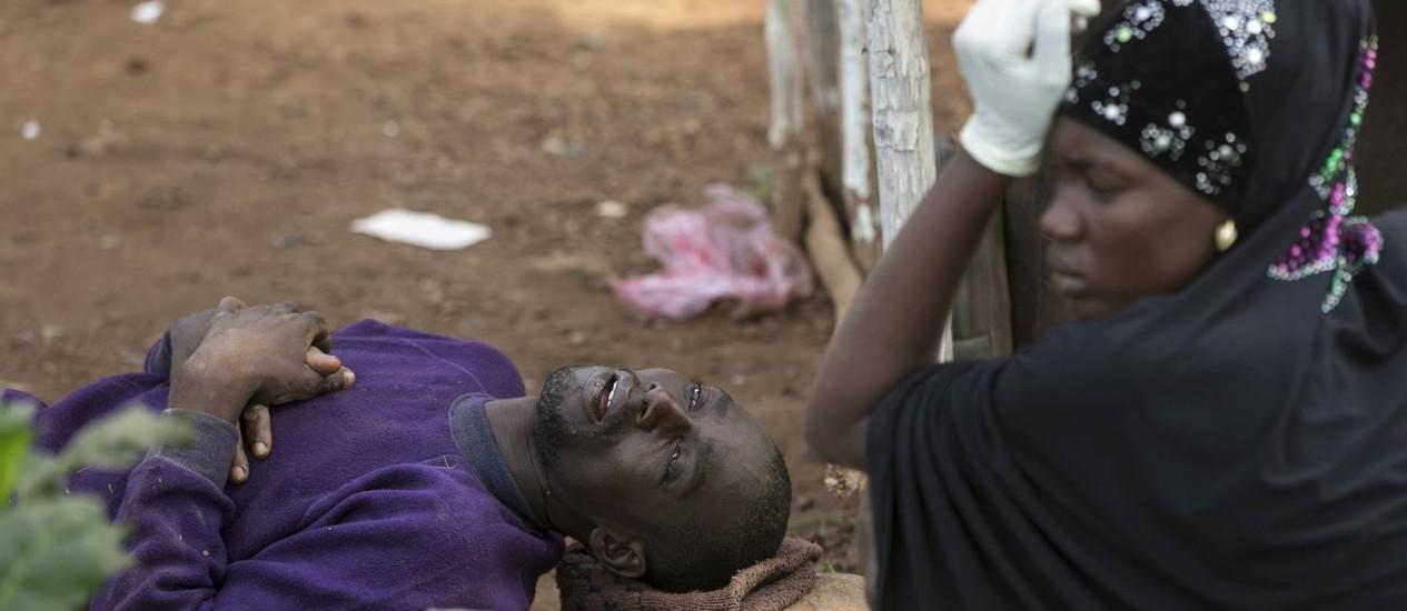 Homem com suspeita de ebola aguarda transporte ao lado da sua mulher em Freetown, Serra Leoa Foto: BAZ RATNER / REUTERS