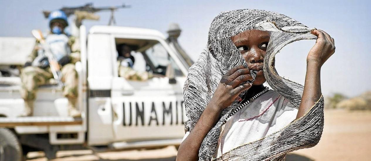 Uma mulher sudanesa se protege do sol, à frente de um veículo blindado da força de paz Unamid, da ONU, na região de Nyoro Foto: NYT/4-2-2014