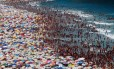 Para suportar o calorão e as areias escaldantes, banhistas transformam a Praia de Copacabana num mar de barracas coloridas