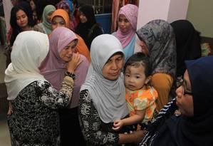 Rohana, mãe de Khairunisa, uma aeromoça que estava viajando no voo QZ 8501, e parentes reúnem-se em sua casa na cidade da Indonésia de Palembang Foto: ABDUL QODIR / AFP