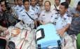 Comandante indonésio apresenta objetos retirados do mar que pertenciam ao voo 8501 da AirAsia, como uma mala azul e o que parece ser um tanque de oxigênio, na base aérea de Pangkalan Bun