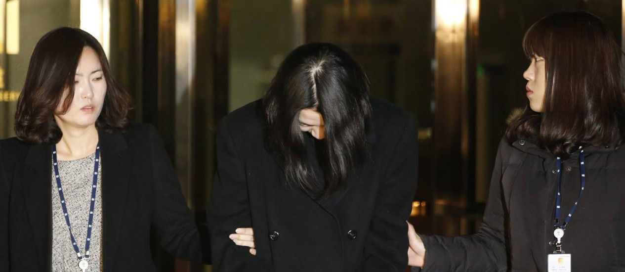 Cho Hyun-ah é levada a delegacia de Seul de cabeça baixa, como apareceu em outros momentos após o incidente Foto: KIM HONG-JI / REUTERS
