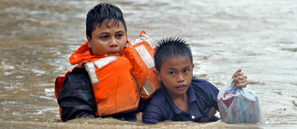 Policial ajuda no resgate de um menino na ilha de Mindanao, nas Filipinas Foto: Erwin Frames / REUTERS