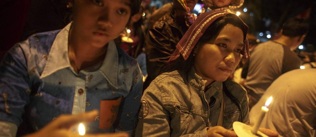 Homenagens. Indonésias carregam velas em vigília para as vítimas do voo QZ8501 da AirAsia: avião perdeu contato antes de desaparecer do radar Foto: ATHIT PERAWONGMETHA / REUTERS