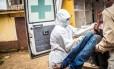 Agentes de saúde colocam suspeito de ter contraído ebola em ambulância na cidade de Freetown, Serra Leoa