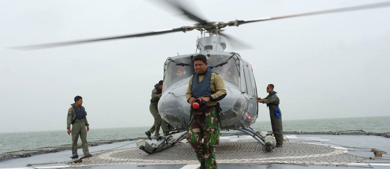 Helicóptero indonésio pousa em navio após mais um voo em tentativa de localizar restos de avião Foto: ADEK BERRY / ADEK BERRY/AFP