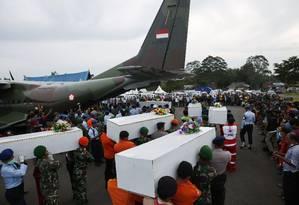 Caixões contendo os restos mortais de passageiros do voo QZ8501 são levados para um avião militar Foto: DARREN WHITESIDE / REUTERS