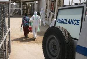 Agente da saúde ampara nova paciente de Ebola em centro de tratamento nos arredores de Freetown, Serra Leoa Foto: Baz Ratner / REUTERS