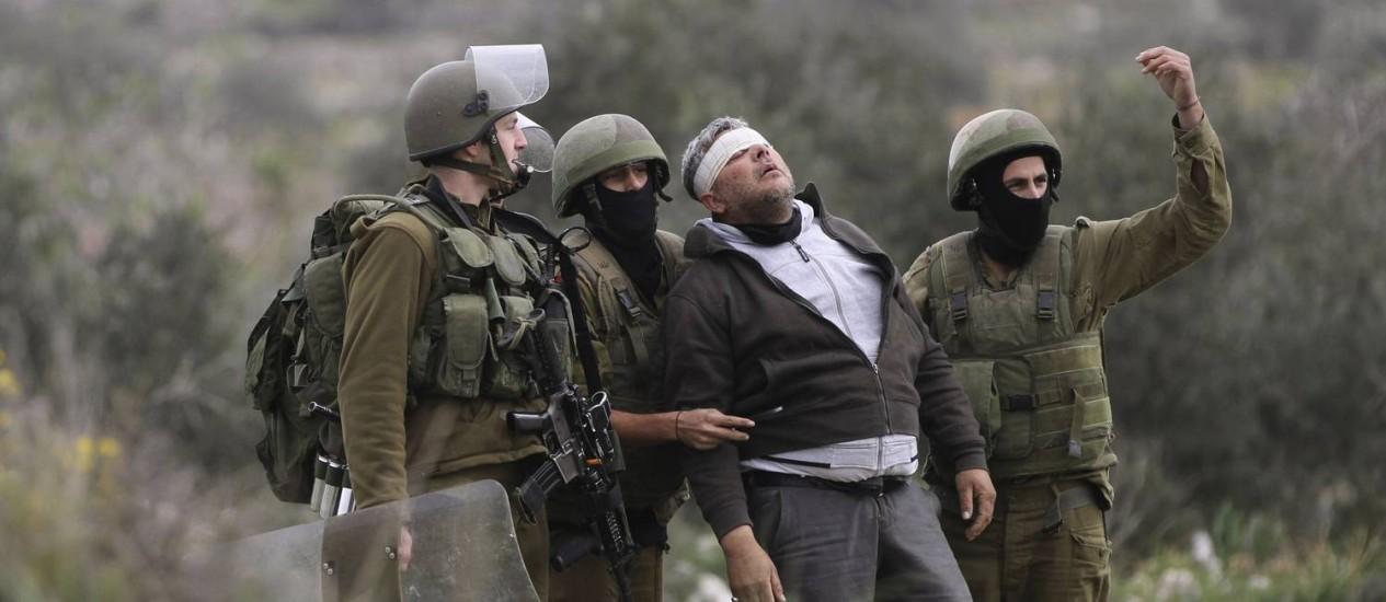Soldados israelense detém manifestante palestino em Qadomem, na Cisjordânia Foto: ABED OMAR QUSINI / REUTERS