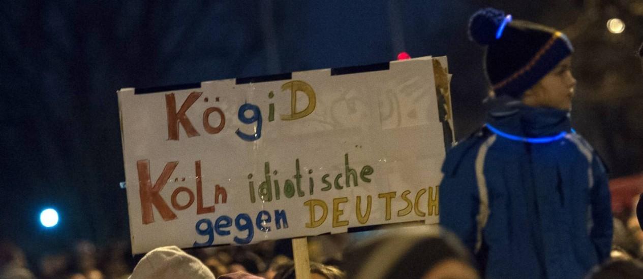 """Manifestante segura cartaz com os dizeres """"Colônia contra os alemães idiotas"""", durante ato de protesto contra manifestações de grupo anti-islâmico na Alemanha Foto: MAJA HITIJ / AFP"""