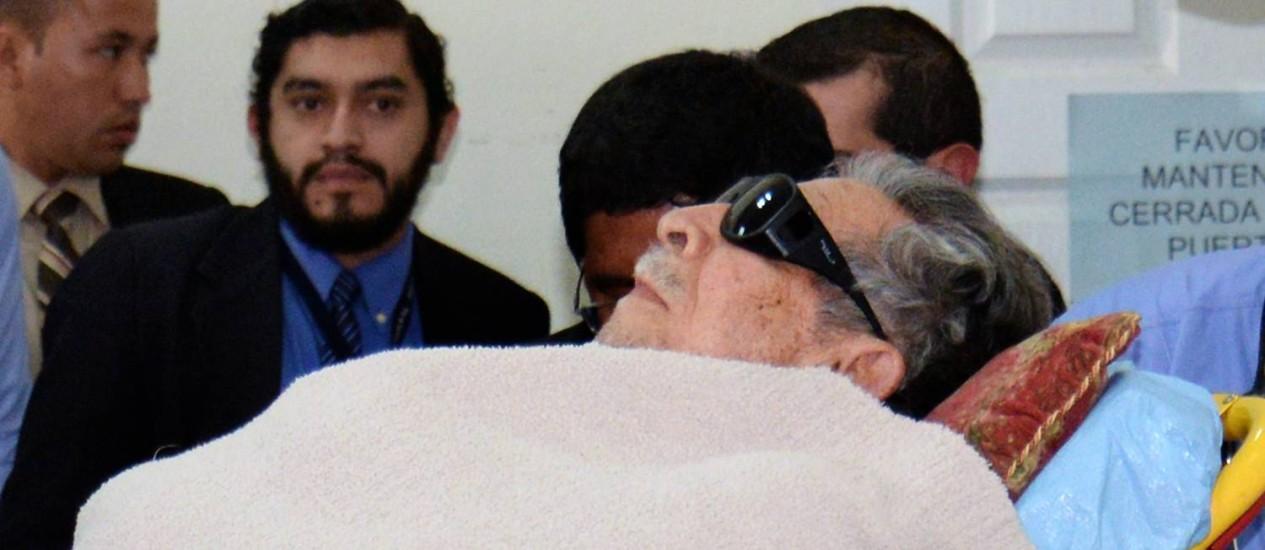 General Jose Efrain Rios Montt, chega em uma maca ao tribunal no qual enfrenta julgamento por crimes contra a Humanidade. Defesa tentou impedir que ex-ditador voltasse ao banco dos réus, mas pedido foi negado Foto: ORLANDO ESTRADA / AFP