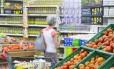Consumidora confere preços em supermercado do Rio