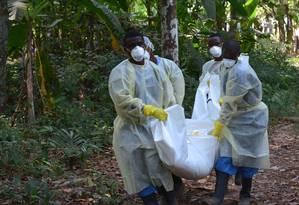 Voluntários carregam corpo de vítima suspeita de ebola Foto: ZOOM DOSSO / AFP