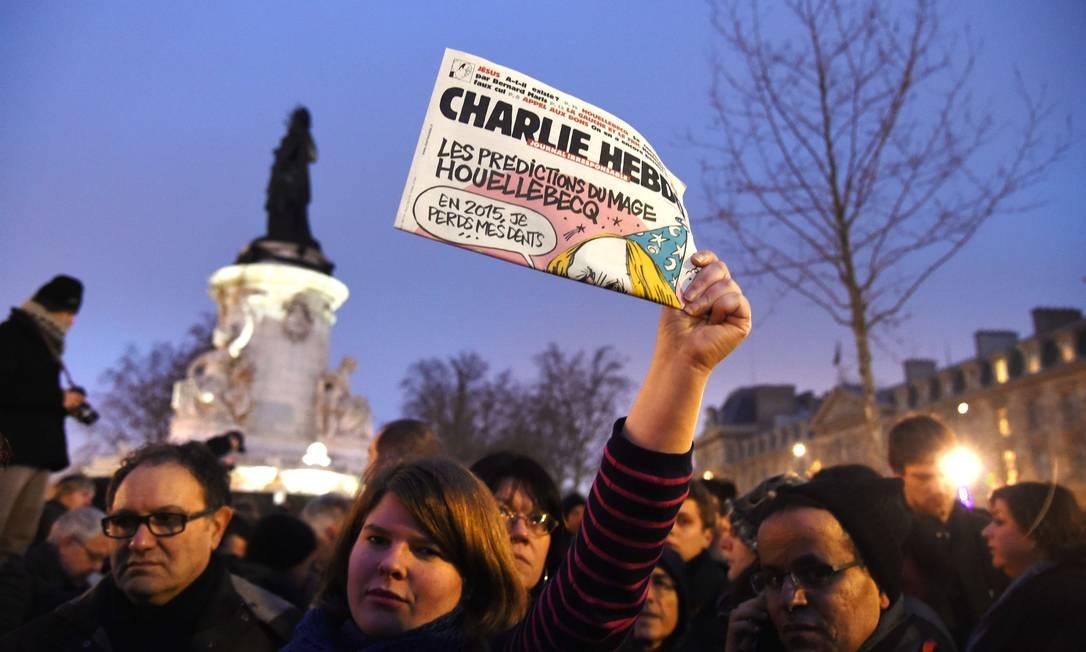 Mulher exibe exemplar do semanário em manifestação em Paris DOMINIQUE FAGET / AFP
