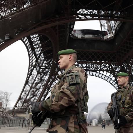 Vigilância redobrada. Soldados franceses, com armamento pesado, fazem patrulha aos pés da Torre Eiffel, símbolo maior de Paris: segurança está reforçada em toda a França Foto: JOEL SAGET/AFP