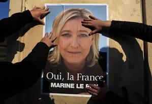 Apoiadores colam cartaz de Marine Le Pen. Candidata de extrema-direita, a eurocética foi favorita em boa parte do período eleitoral na França Foto: REUTERS/18-3-2014