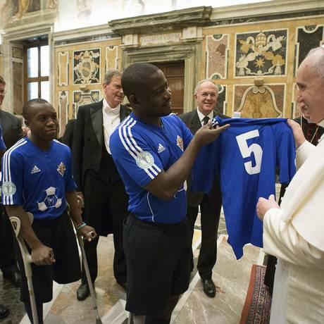 No Vaticano, Papa Francisco recebe camisa de futebol de haitiano que sobreviveu a terremoto de 2010 no Haiti Foto: OSSERVATORE ROMANO / REUTERS