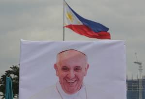 Cartaz com a foto do Papa Francisco é visto sob a bandeira das Filipinas na capital Manila: país é o único de maioria católica na Ásia e um dos destinos da segunda viagem do Pontífice à região em menos de seis meses Foto: AP/Aaron Favila