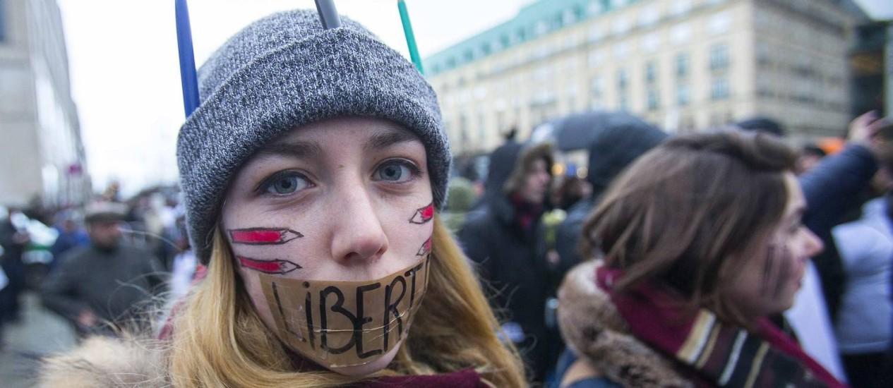 """Manifestante na marcha em Paris cobriu a boca com uma fita escrita com a palavra """"liberdade"""": presença no protesto de representantes de países que perseguem a imprensa causou revolta de organizações que lutam pela liberdade de expressão Foto: REUTERS/HANNIBAL HANSCHKE"""