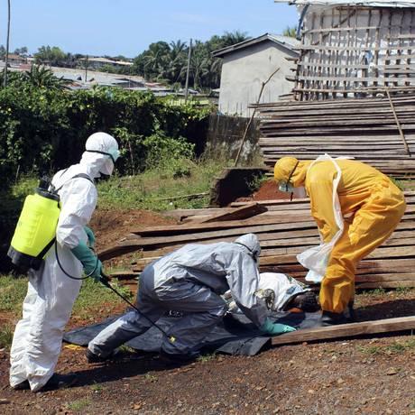Profissionais de saúde recolher corpo de mulher que morreu vítima do ebola em Serra Leoa Foto: STRINGER/ 14-10-2014 / REUTERS