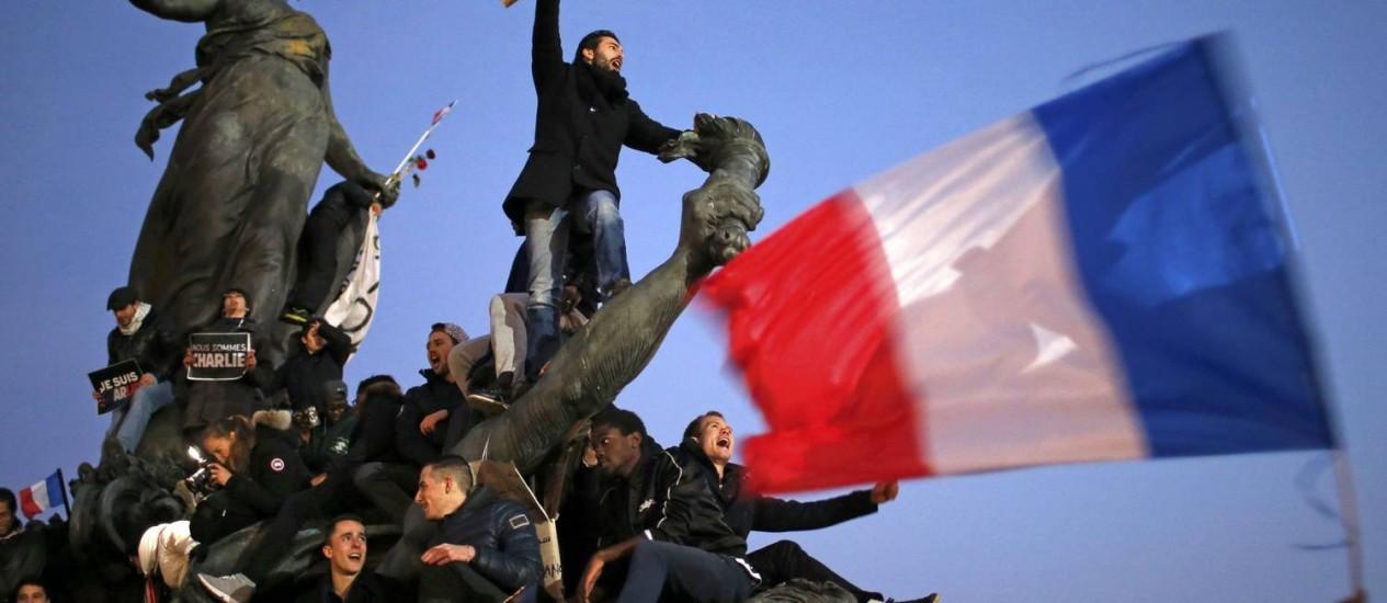 Vários manifestantes, um deles com um lápis gigante em punho, sobem em cima de uma estátua durante a 'Marcha Republicana', no último domingo, em Paris Foto: REUTERS / STEPHANE MAHE