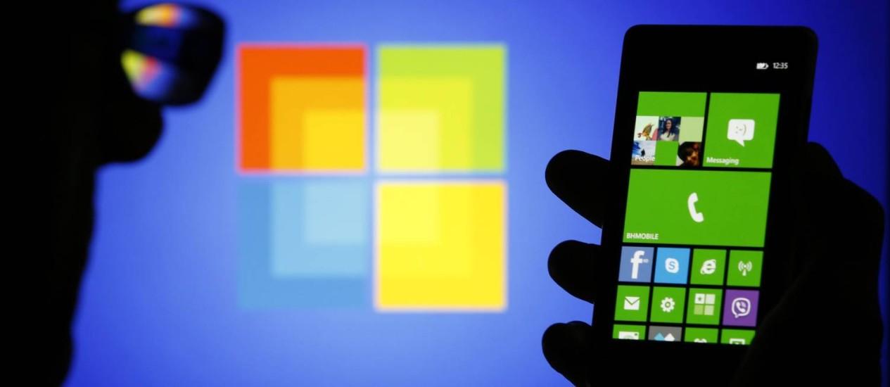Um homem observa um celular Nokia com o logo da Microsoft ao fundo: reclamação contra o Google Foto: DADO RUVIC / REUTERS