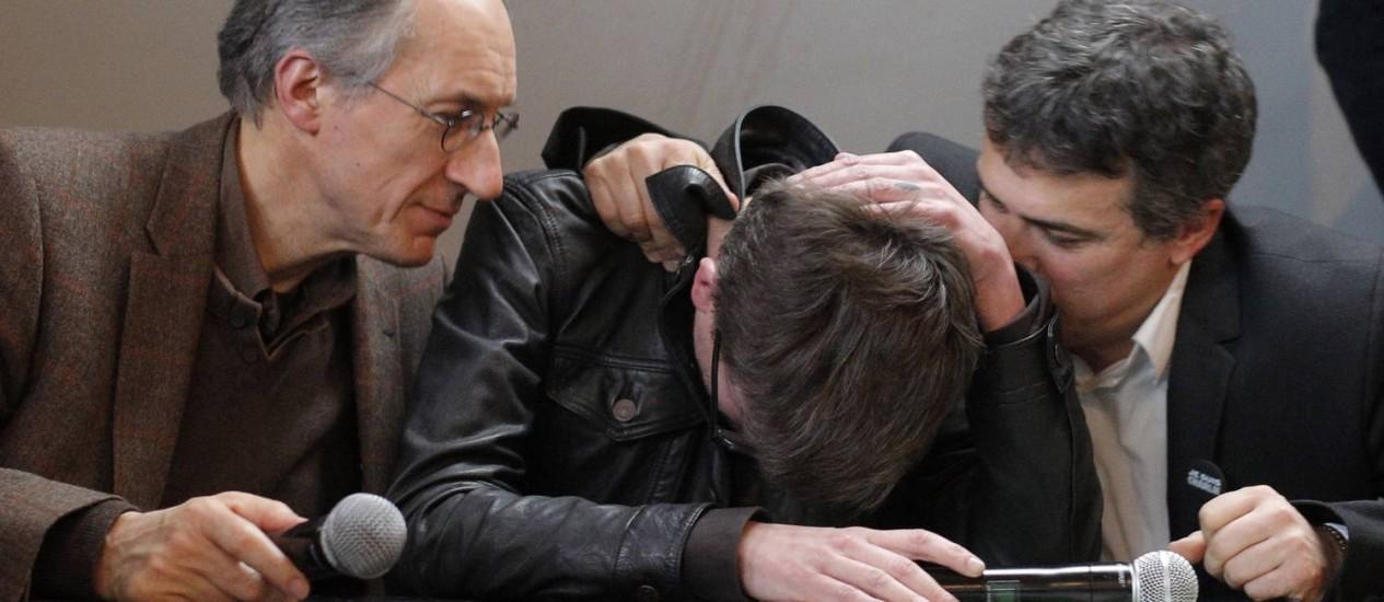 """Na entrevista coletiva, o novo editor-chefe do """"Charlie Hebdo"""", Gerard Biard (esquerda), conforta o cartunista Luz, com o colunista Patrick Pelloux Foto: AP"""