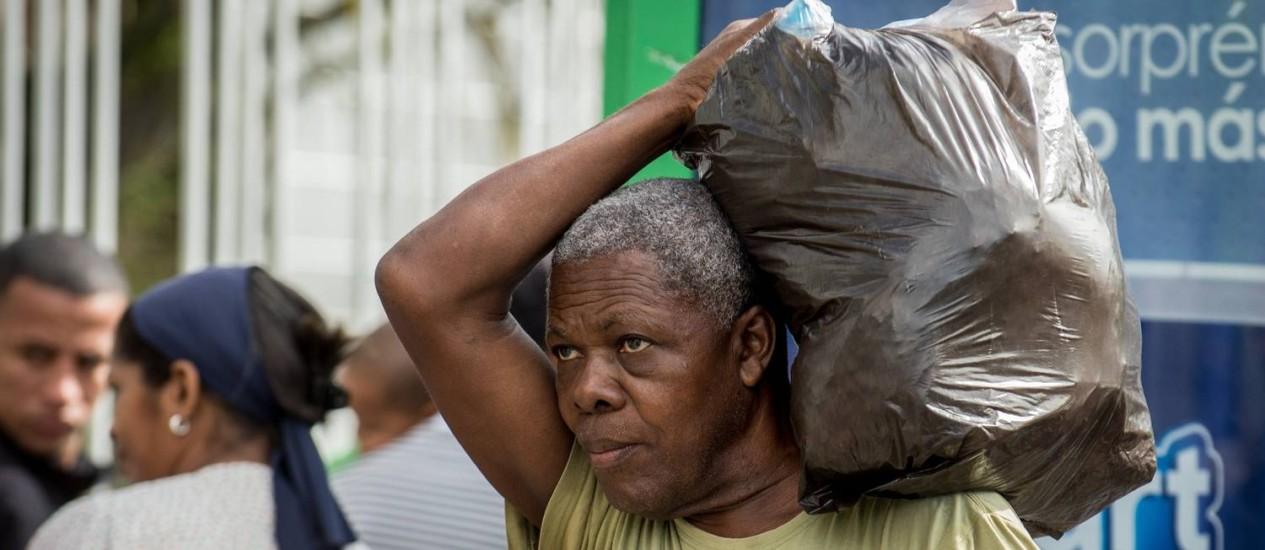 Homem carrega sacola na saída de supermercado na Venezuela. Ação contra o contrabando levou autoridades a deportarem mais de 100 cidadãos colombianos Foto: FEDERICO PARRA / AFP