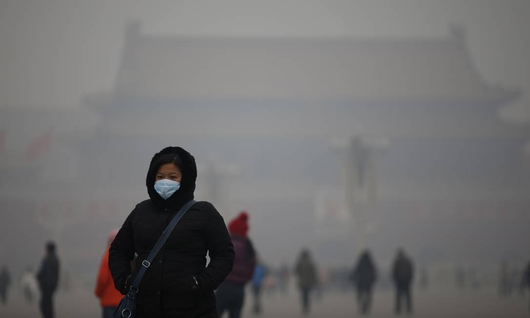 Sofrimento: mulher usa máscara para se proteger da densa poluição em Pequim nesta quinta-feira, o que levou o governo chinês a emitir o primeiro alerta de saúde a ela relacionado deste ano Foto: REUTERS/KIM KYUNG-HOON