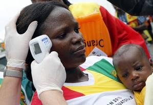 Cuidados. Mulher passa por checagem de temperatura em um estádio na Guiné: esforços contra a doença devem ser mantidos Foto: AMR ABDALLAH DALSH / REUTERS/ 20-01-2015