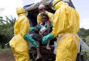 Agentes de saúde carregam paciente suspeita de ebola na Guiné Foto: KENZO TRIBOUILLARD / AFP