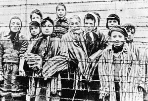 Crianças recém-libertadas em janeiro de 1945 atrás de cerca de arame farpado em Auschwitz: no fim, prisioneiros eram até cremados vivos no campo de concentração, tamanha era a pressa dos carrascos nazistas Foto: SUB / AP
