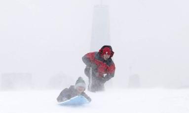 Moradores de Jersey City, em Nova Jersey, brincam na neve. Cinco estado da regiao da Nova Inglaterra, na Costa Leste dos EUA, declararam estado de emergência nesta segunda-feira Foto: Julio Cortez / AP
