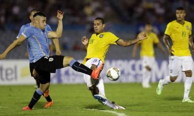 Lucas e o uruguaio Cabaco disputam a bola na partida em Montevidéu Foto: JORGE ADORNO / Reuters
