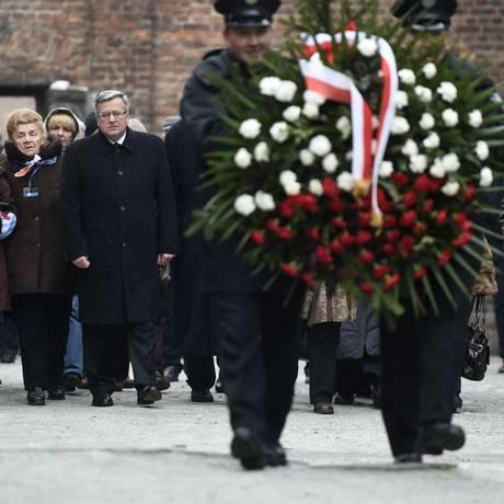 Presidente polonês Bronislaw Komorowski e sobreviventes de Auschwitz acompanham coroa de flores Foto: ODD ANDERSEN / AFP