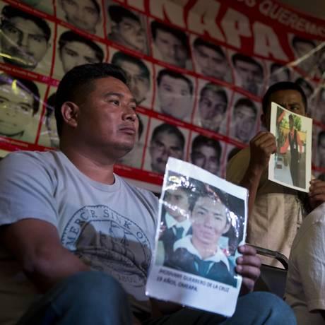 Parentes de estudantes exibem imagens em memorial Foto: RONALDO SCHEMIDT / AFP