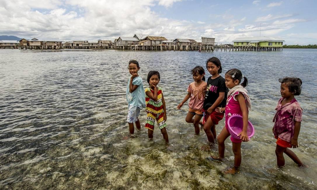 Crianças andam em frente à vila de Torosiaje, na Indonésia: busca por recursos marinhos leva adultos a buscarem emprego na indústria pesqueira, enquanto mães recorrem à mendicância nas cidades, onde ganham US$ 1 por dia Foto: Divulgação/James Morgan /